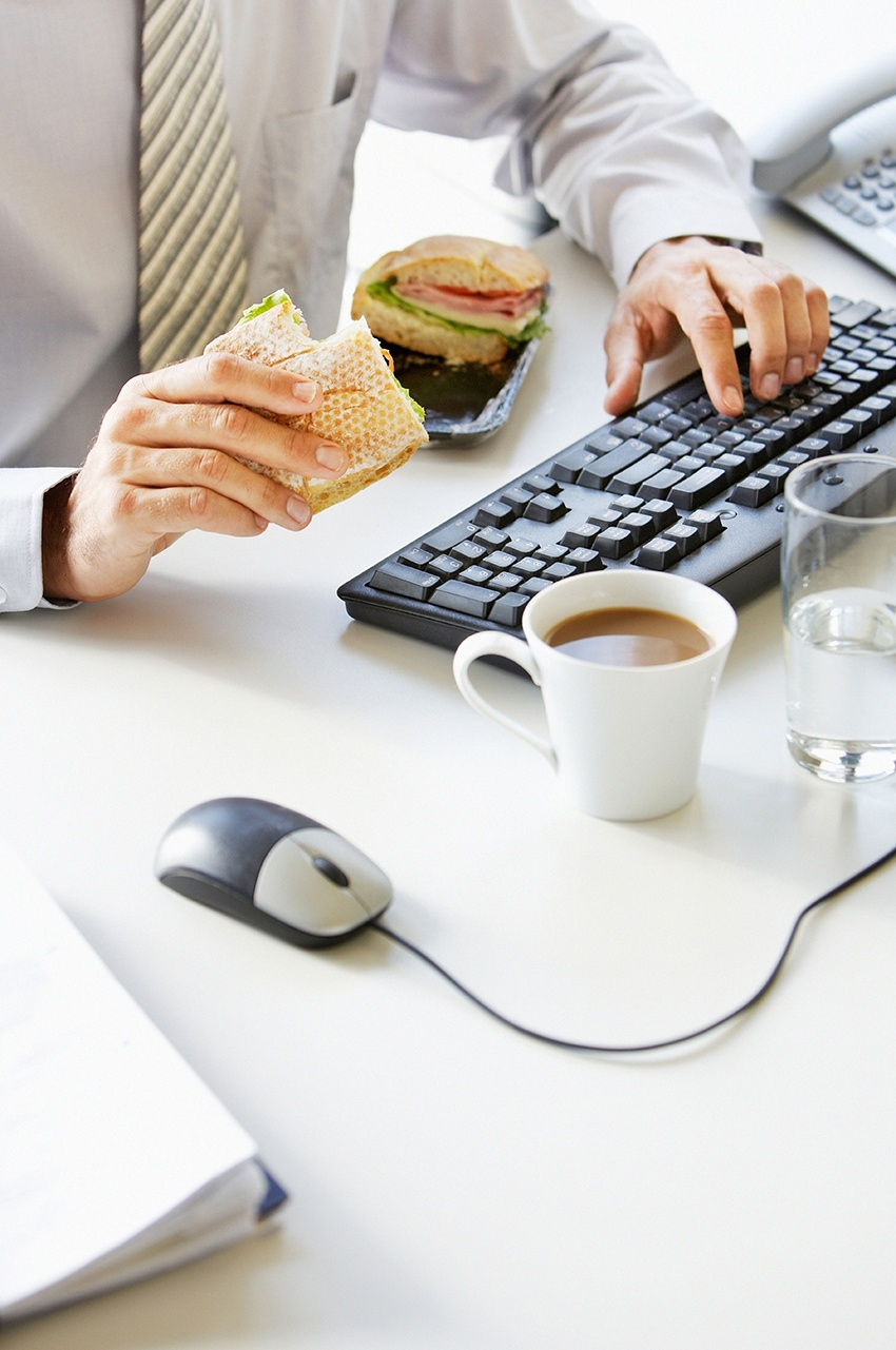 An office worker eating and drinking at their desk