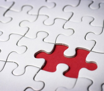 A white jigsaw with a puzzle piece missing